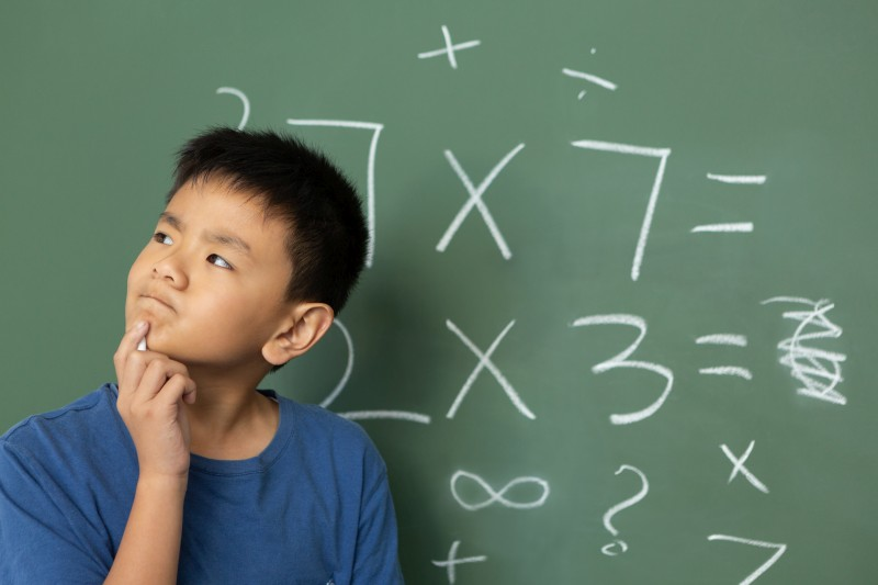 boy thinking mathematic in front of chalkboard