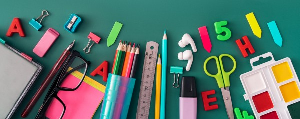 Office stationery, headphones, glasses and paints on green background