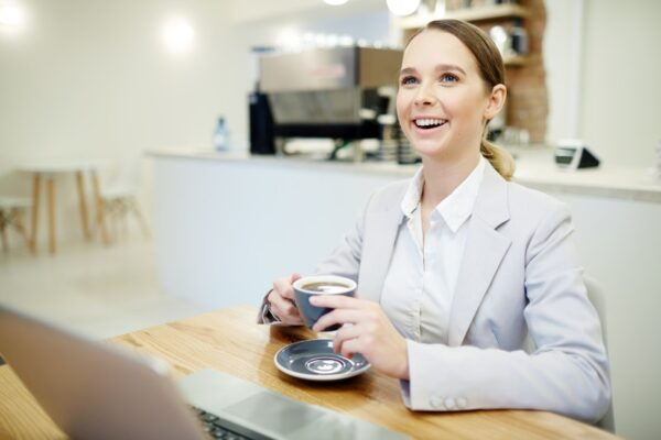 Wanita minum kopi depan laptop di kafe