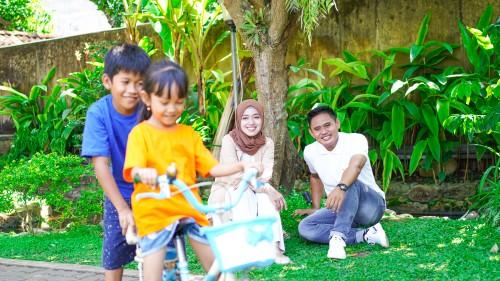 Anak-anak bermain basikal di luar ditemani ibu bapa